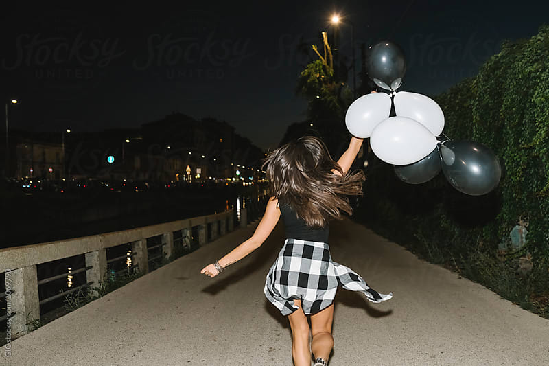 Woman running with balloons in the night party by GIC for Stocksy United