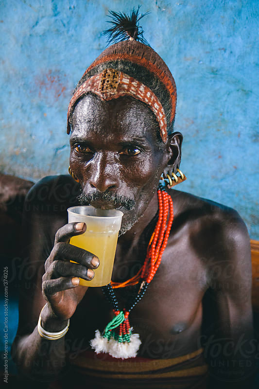 Hamer tribe senior man with traditional clothes having a drink on a local bar. Omo Valley, Ethiopia by Alejandro Moreno de Carlos for Stocksy United