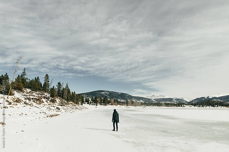 Man walking across frozen lake by Isaiah & Taylor Photography for Stocksy United