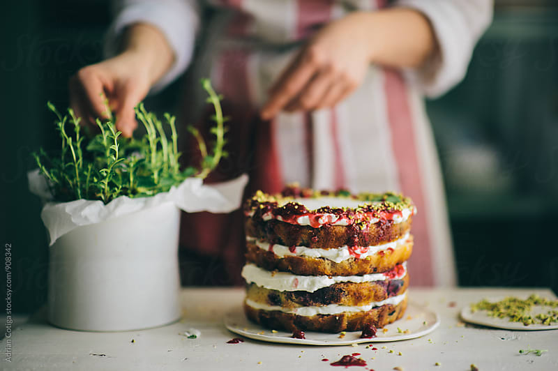 Delicious cake; naked cake with berries and whipped cream decorated with mint leaves by Adrian Cotiga for Stocksy United
