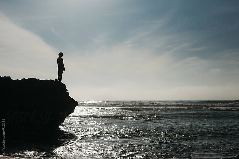 Girl watching the ocean waves from a rock above in the summertime by paff for Stocksy United