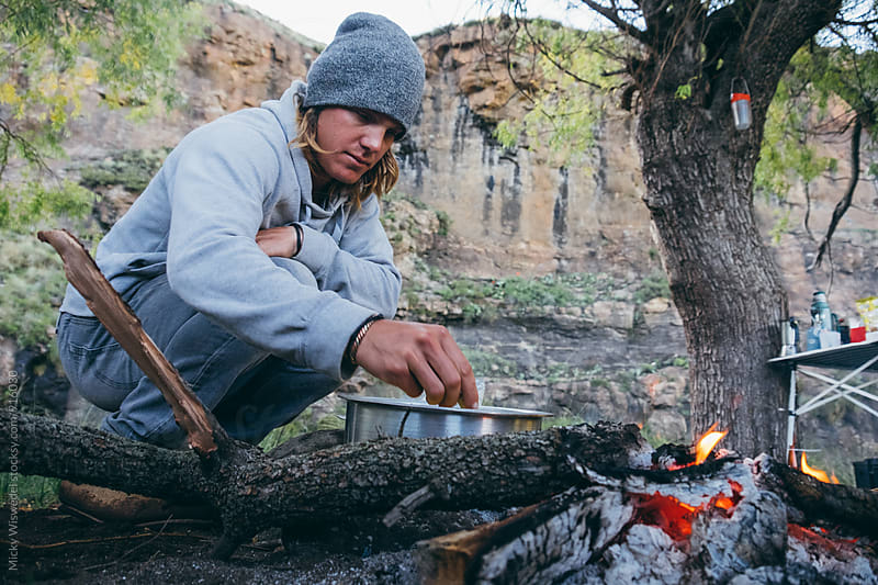 man cooking by a camp fire in the mountains by Micky Wiswedel for Stocksy United