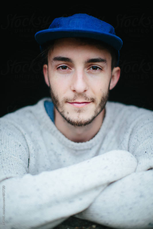 Portrait of a young man in a blue hat  by HOWL for Stocksy United