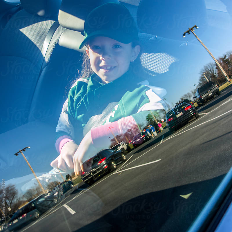 Young Girl in Car Back Seat Ready to Play Tee Ball by Brian McEntire for Stocksy United