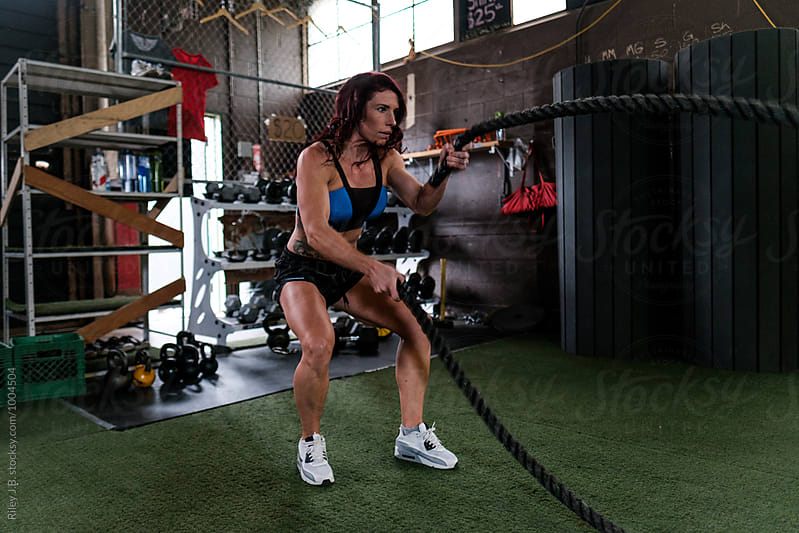A fit woman uses battling ropes in a gritty gym by Riley J.B. for Stocksy United