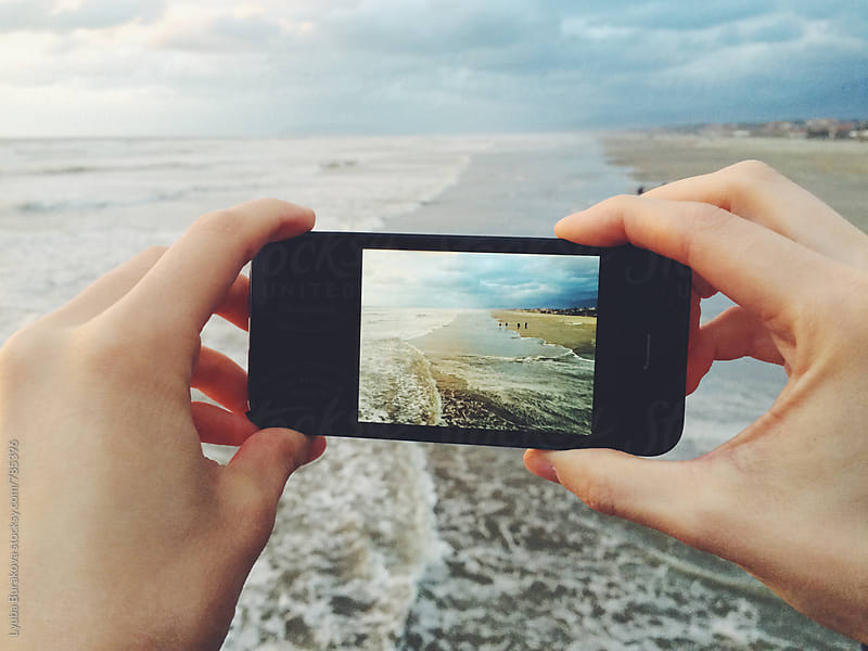 Woman taking photo of the sea on smartphone by Lyuba Burakova for Stocksy United