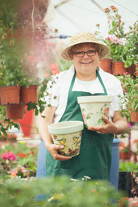 Smiling Florist Holding Flower Pots by Lumina for Stocksy United