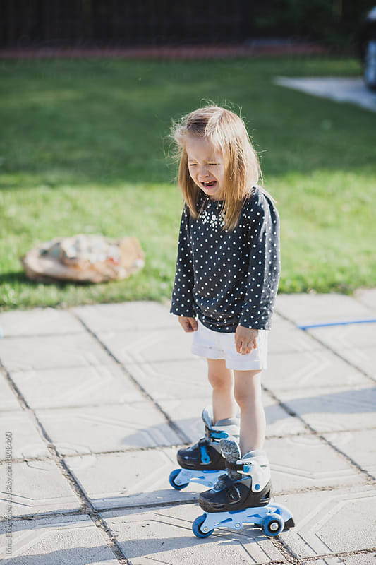 Crying girl standing on roller skates by Irina Efremova for Stocksy United