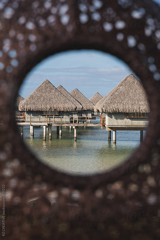 Over water bungalows in the shallow water of the lagoon in Tahiti. by Robert Zaleski for Stocksy United