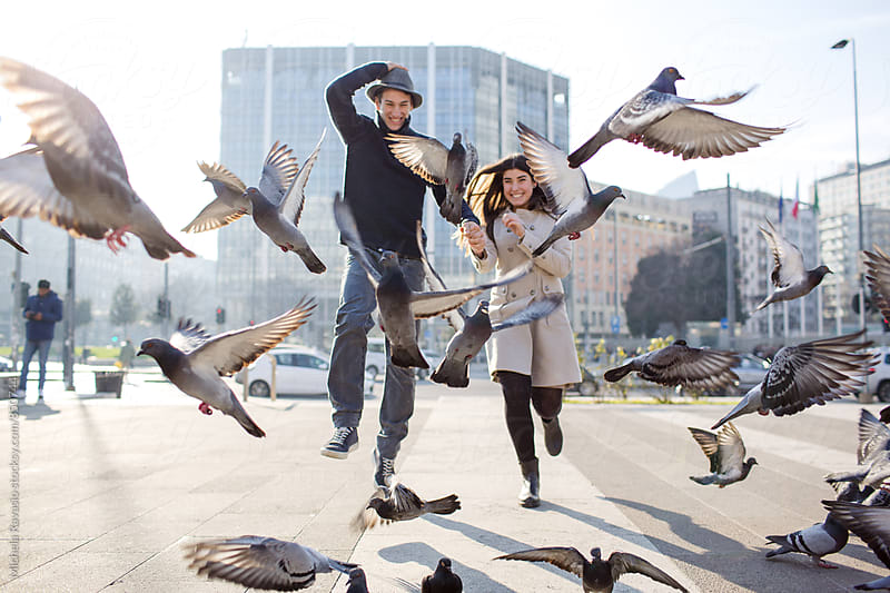 Happy couple runs through the pigeons by michela ravasio for Stocksy United