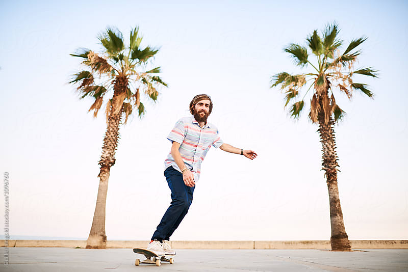 Smiling skater riding on road against of two palm trees by Guille Faingold for Stocksy United