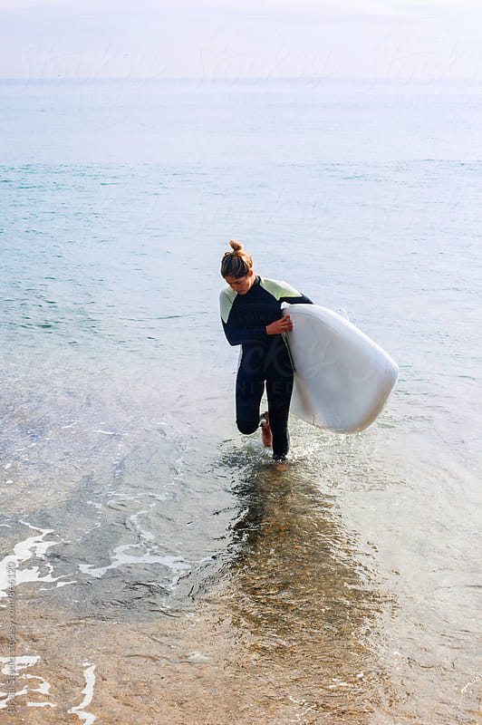Blonde girl walking out the sea with a paddle board  by Bisual Studio for Stocksy United