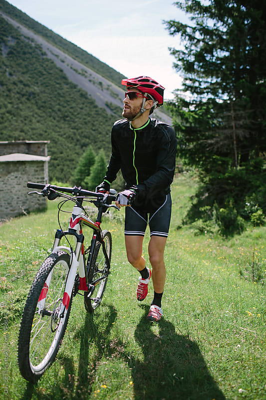Cyclist with his bike in the mountains by Davide Illini for Stocksy United