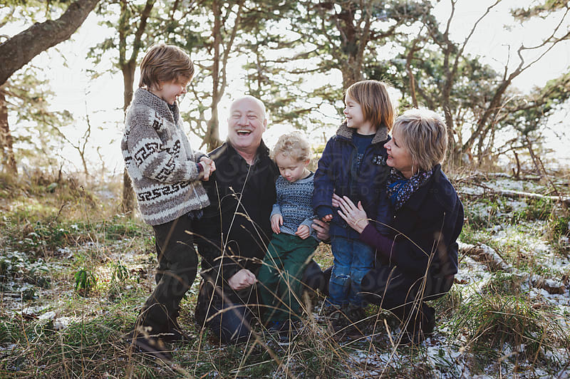 Happy grandparents enjoying their grand children outside in winter - family portrait by Rob and Julia Campbell for Stocksy United