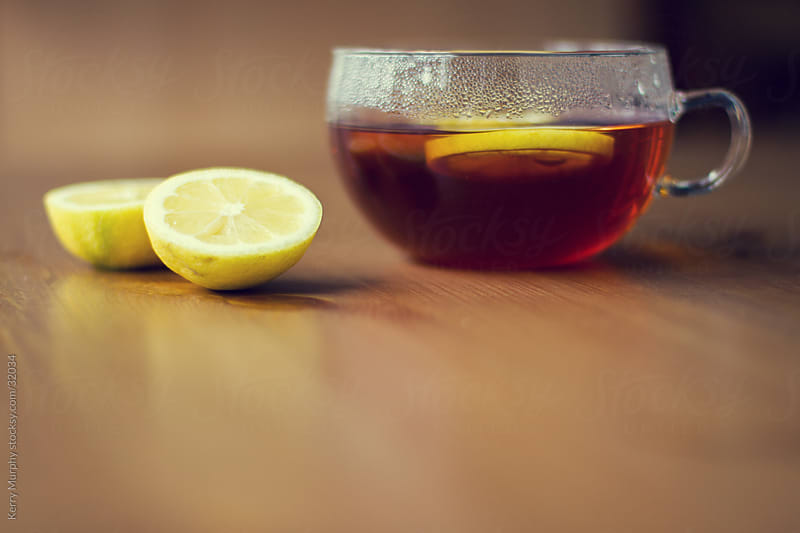 Hot tea in glass mug with lemon slices by Kerry Murphy for Stocksy United