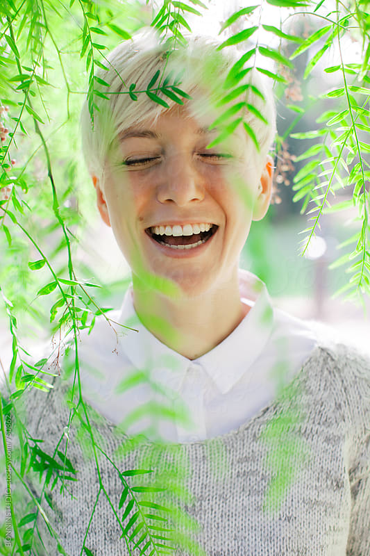 Portrait of a woman laughing between green leaves. by BONNINSTUDIO for Stocksy United