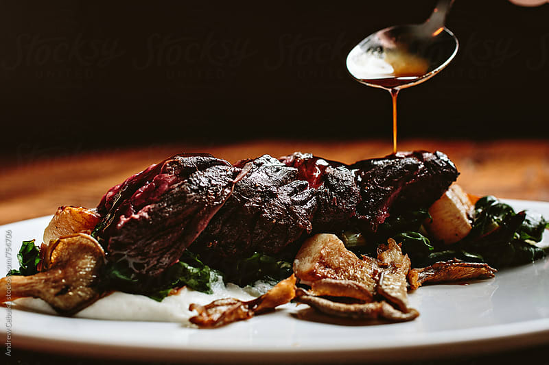 steak being sauced - digital file by Andrew Cebulka for Stocksy United