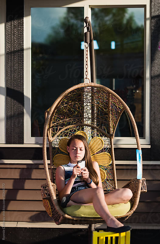 Teen Girl Texting In Hanging Chair Outdoors by Ronnie Comeau for Stocksy United