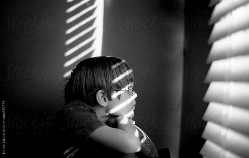 Boy looking out of a window by Kirstin Mckee for Stocksy United