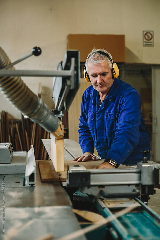 carpenter with yellow protection earmuffs working on a benchsaw
