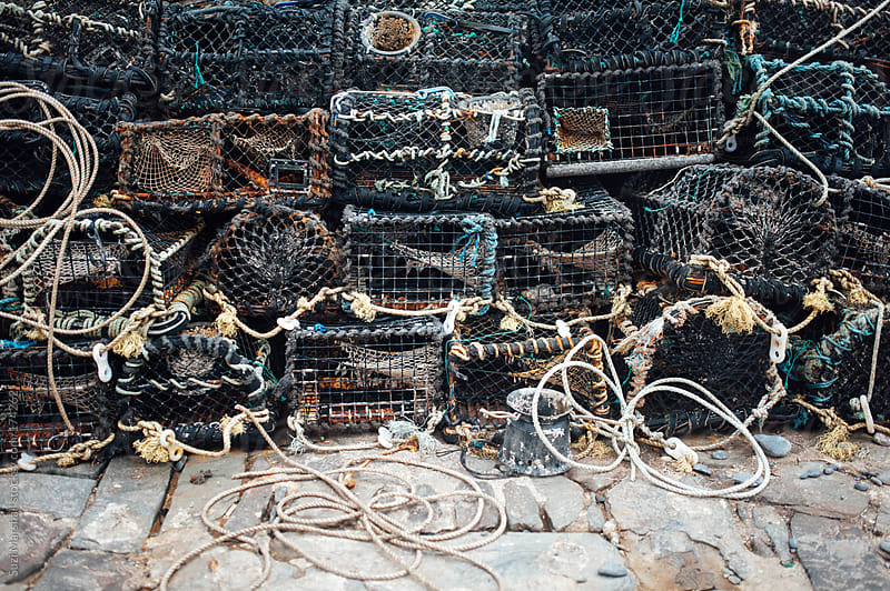 Crab and lobster pots stacked against a stone wall by Suzi Marshall for Stocksy United