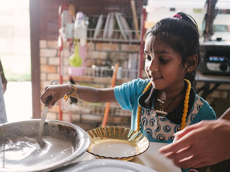 Happy indian girl helping in kitchen by Martin Matej for Stocksy United