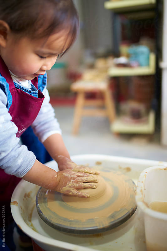 lovely little asian girl busy in the pottery by Bo Bo for Stocksy United