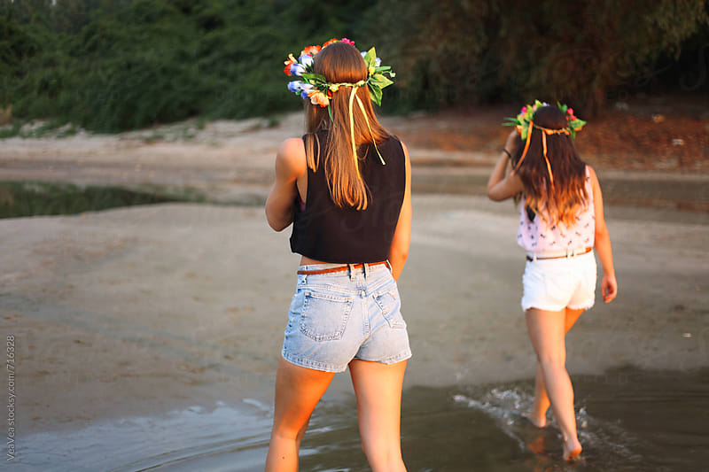 Two young women from the back on the river beach  by VeaVea for Stocksy United