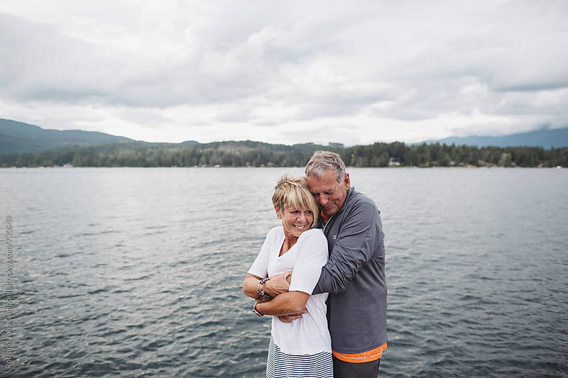 Fun, mature couple hugging together on dock at the lake by Rob and Julia Campbell for Stocksy United