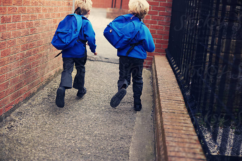 Two school children running to school by sally anscombe for Stocksy United