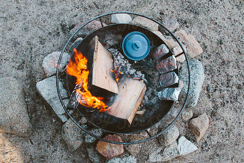 Cooking camp food in a fire ring on the beach by Justin Mullet for Stocksy United