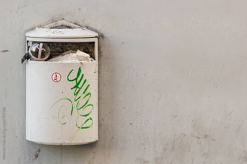 Overflowing trashbin on a wall by Melanie Kintz for Stocksy United