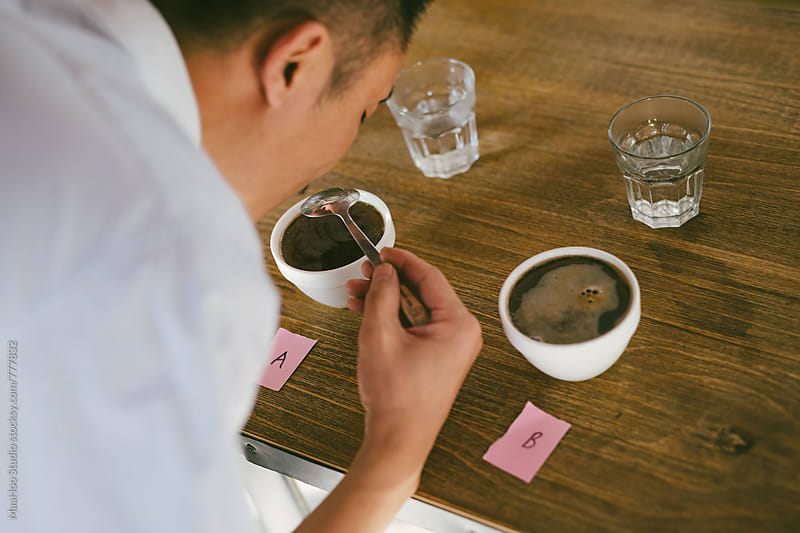 Young man making experiment on coffee and comparing by MaaHoo Studio for Stocksy United