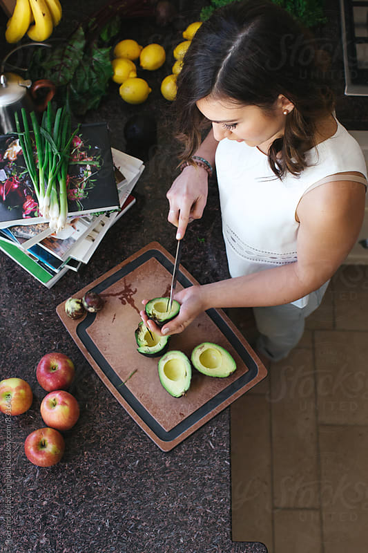 Young woman in kitchen preparing food - slicing avocados by Rob and Julia Campbell for Stocksy United