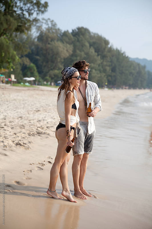 Couple standing together at the beach by Jovo Jovanovic for Stocksy United