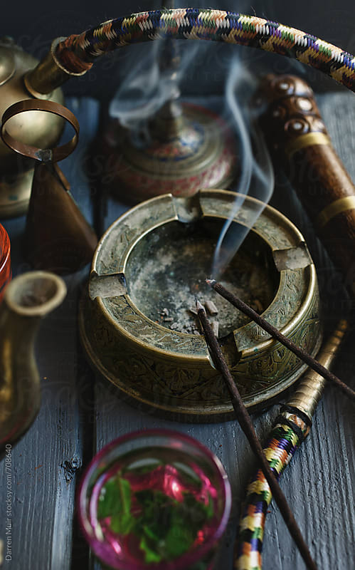 Incense sticks burning and smoking in a still life setting.  by Darren Muir for Stocksy United