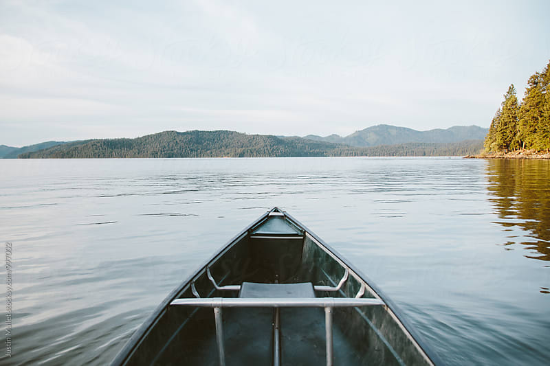 Canoeing across a smooth lake by Justin Mullet for Stocksy United