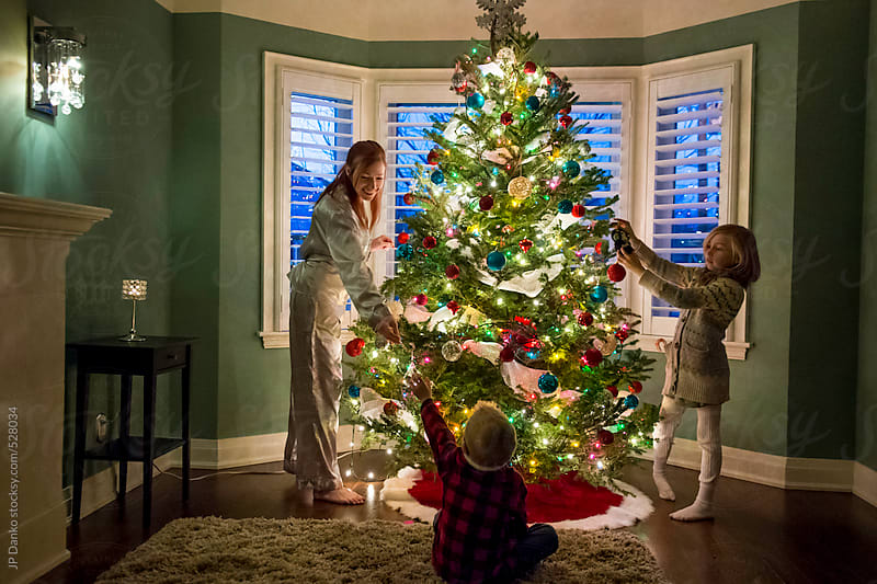 Family Boy Girl and Mother Decorating Christmas Tree In Living Room by JP Danko for Stocksy United