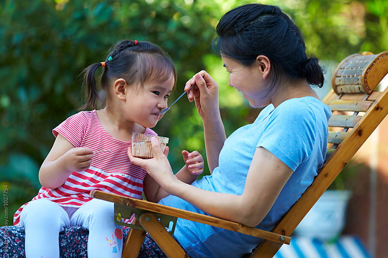happy little asian girl eating ice cream  with her mother by Bo Bo for Stocksy United