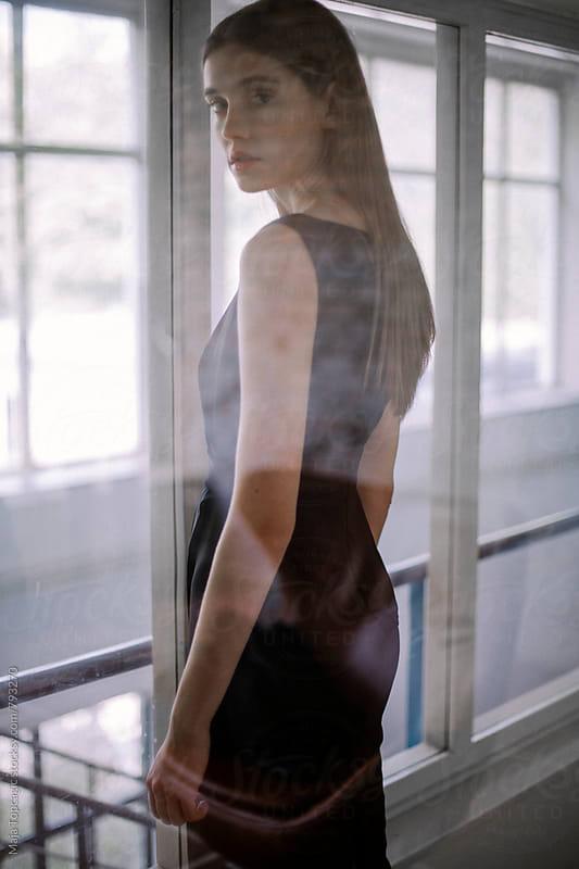 Beautiful woman looking through a window by Maja Topcagic for Stocksy United