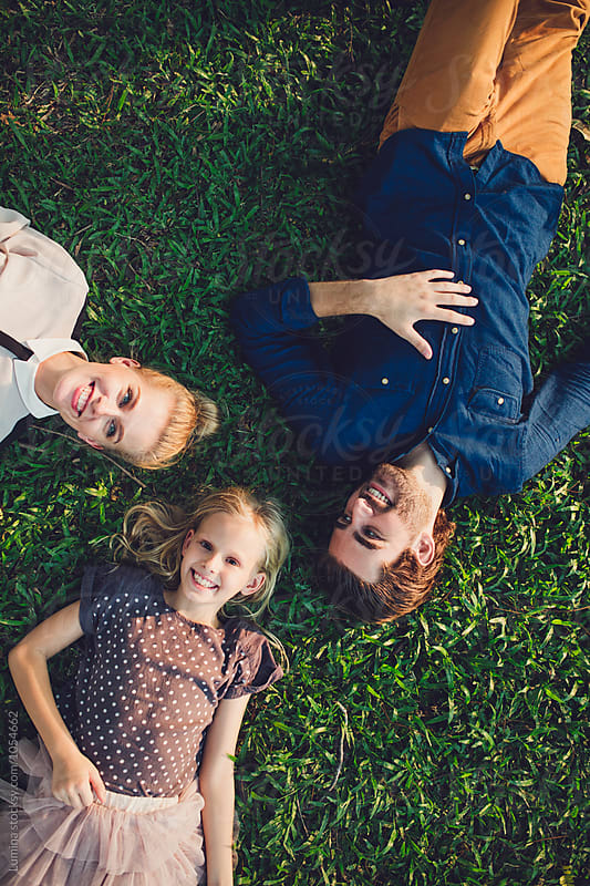 Family Lying on a Grass by Lumina for Stocksy United