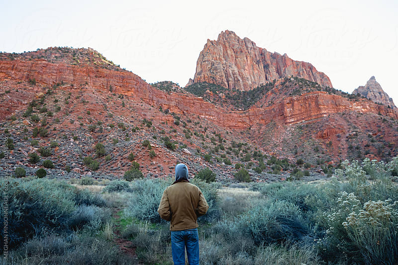 Man in Hoodie Looks over Red Rock Peaks by MEGHAN PINSONNEAULT for Stocksy United