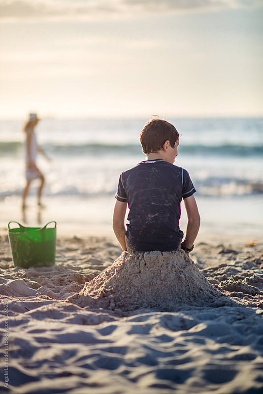 Boy sitting on a sand castle at the beach by Angela Lumsden for Stocksy United