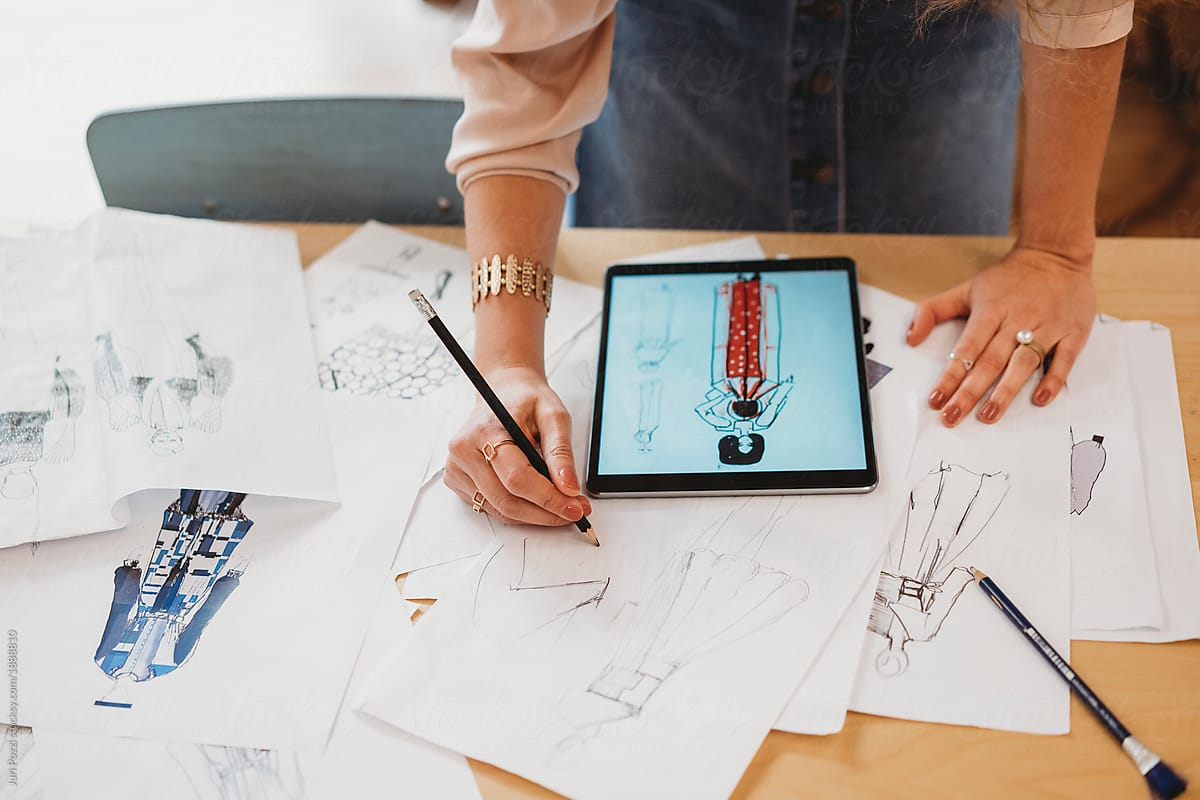 Young Female Fashion Designer Uses Her Tablet To Make Fashion Sketches By Juri Pozzi Designer Fashion Stocksy United