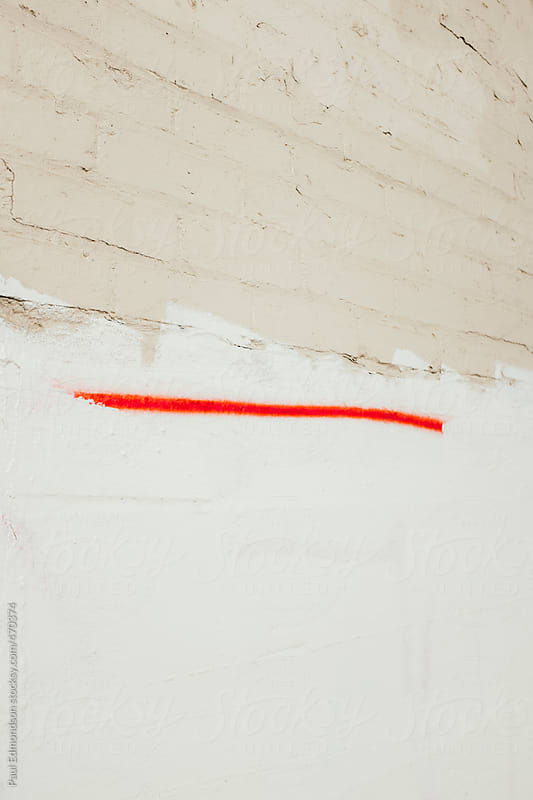 A single line of red spray paint on building wall exterior by Paul Edmondson for Stocksy United
