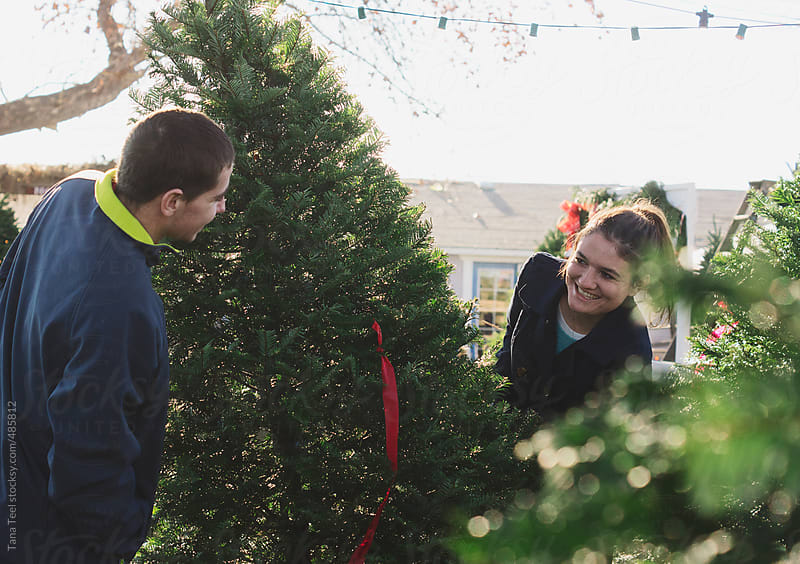 Young couple peek at each other from around a Christmas tree by Tana Teel for Stocksy United