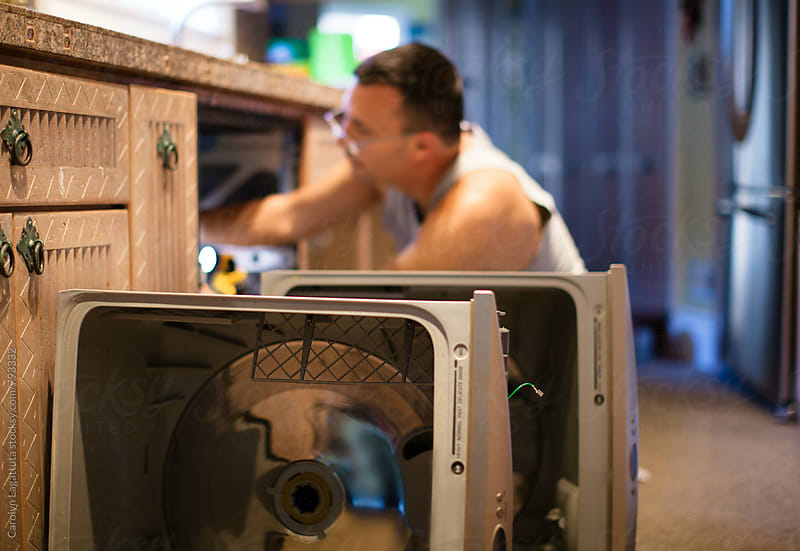 Man fixing a double drawer dishwasher in his home by Carolyn Lagattuta for Stocksy United