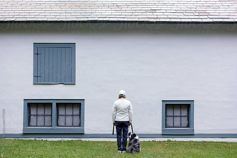 A woman and her dog stand in front of an old barn. by Holly Clark for Stocksy United