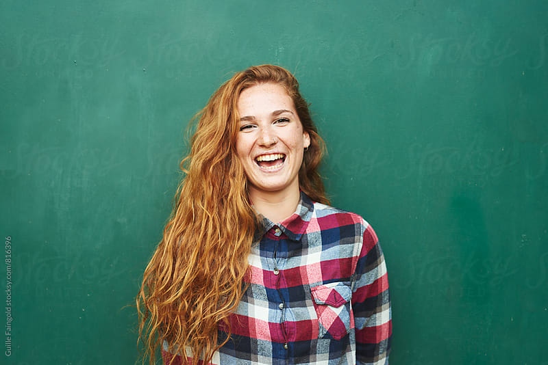 Portrait of red-haired woman smiling at camera by Guille Faingold for Stocksy United