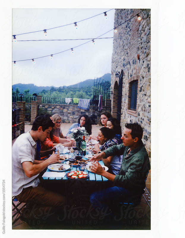 Instant shot of friends having dinner at patio by Guille Faingold for Stocksy United